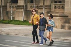 Stilfulla asiatiska vänner som korsar gatan Arkivbilder