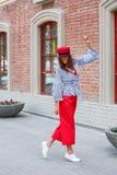 Stilfulla den iklädda brunettflickan en randig blus, röda breda flåsanden och ett rött lock poserar i stadsgatan på en solig dag royaltyfri fotografi
