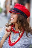 Stilfulla den iklädda brunettflickan en randig blus, röda pärlor och ett rött lock poserar i stadsgatan på en solig dag arkivbilder