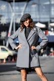 Stilfulla den iklädda brunettflickan en trendig grå klänning, ett grått omslag och ett lock poserar i stadsgatan på det soligt arkivbild