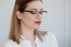 Stilfulla exponeringsglas i en tunn ram, visionkorrigering St?ende av en ung kvinna arkivfoto