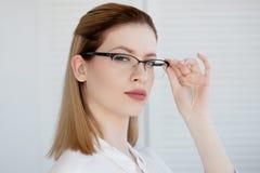 Stilfulla exponeringsglas i en tunn ram, visionkorrigering St?ende av en ung kvinna arkivbilder