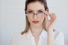 Stilfulla exponeringsglas i en tunn ram, visionkorrigering St?ende av en ung kvinna arkivfoton