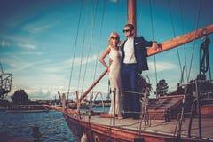 Stilfulla förmögna par på en lyxig yacht Arkivbild