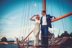 Stilfulla förmögna par på en yacht Arkivbild