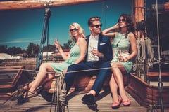 Stilfulla förmögna vänner på en lyxig yacht Royaltyfria Foton