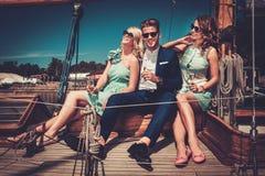 Stilfulla förmögna vänner som har gyckel på en yacht arkivfoton