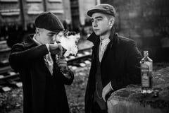 Stilfulla gangster som röker i tweed, utrustar att posera på bakgrundsnolla Royaltyfri Bild