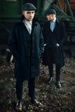 Stilfulla gangstermän i retro kläder som poserar på bakgrund av rommar Royaltyfria Foton