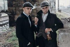 Stilfulla gangstermän som röker posera på bakgrund av järnvägen Royaltyfria Bilder