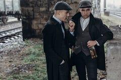 Stilfulla gangstermän som röker posera på bakgrund av järnvägen Fotografering för Bildbyråer