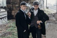 Stilfulla gangstermän som röker posera på bakgrund av järnvägen Arkivbilder
