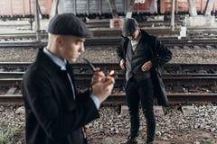Stilfulla gangstermän som röker röret på bakgrund av järnvägen en Arkivbild