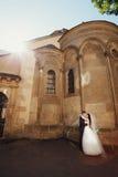 Stilfulla härliga par på bakgrunden av den gamla stenen kyrktar Royaltyfria Bilder