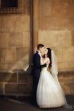 Stilfulla härliga par på bakgrunden av den gamla stenen kyrktar Royaltyfri Foto