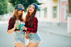 Stilfulla hipsterflickor som tillsammans poserar och dricker coctailar arkivbild