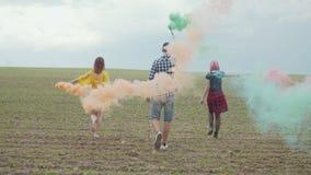 Stilfulla hipsters som går över fält i kulör rök