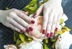 Stilfulla modekvinnors röda manikyr med konstgjorda blommor Pion royaltyfri fotografi