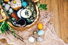 Stilfulla påskägg, easter brödkaka, skinka, beta, korv, smör, gröna filialer i vide- korg på lantligt tyg med våren arkivfoton