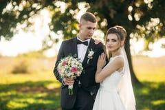 Stilfulla par av lyckliga nygifta personer som går i fält på deras bröllopdag med buketten I mitt av fältet finns det royaltyfri bild