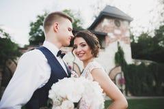 Stilfulla par av lyckliga nygifta personer som går i parkera på deras bröllopdag med buketten Arkivfoton