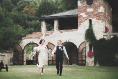 Stilfulla par av lyckliga nygifta personer som går i parkera på deras bröllopdag med buketten Fotografering för Bildbyråer