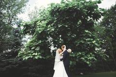 Stilfulla par av lyckliga nygifta personer som går i parkera på deras bröllopdag med buketten Royaltyfri Foto