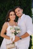 Stilfulla par i vit kläderwalkink i parkerar Brudgum och brud i deras bröllopdag Charma flickan och stiligt arkivfoto