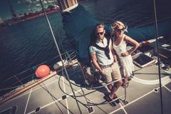 Stilfulla par på en yacht Fotografering för Bildbyråer