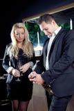 Stilfulla par som öppnar en flaska av champagne Arkivfoto