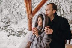 Stilfulla par som rymmer varmt te i koppar och ser vintersno royaltyfria foton