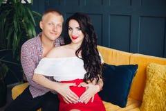 Stilfulla par som sitter på den gula soffan och ser kameran royaltyfri fotografi
