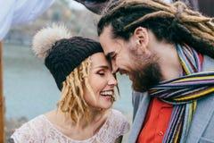 Stilfulla parnygifta personer ler och rörande pannor som står för en sjö Höstbröllopceremoni utomhus Brud Royaltyfri Bild
