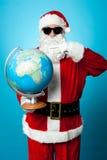 Stilfulla Santa i mörka kupor som pekar på jordklotet Royaltyfria Bilder