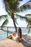 Stilfulla sinnliga kvinnan för barn som den ganska poserar på den fantastiska tropiska stranden med det blåa havet, tycker om hen arkivbild