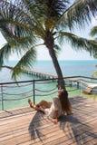 Stilfulla sinnliga kvinnan för barn som den ganska poserar på den fantastiska tropiska stranden med det blåa havet, tycker om hen arkivfoto