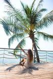 Stilfulla sinnliga kvinnan för barn som den ganska poserar på den fantastiska tropiska stranden med det blåa havet, tycker om hen arkivfoton