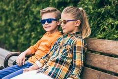 stilfulla små ungar i solglasögon som sitter på bänk royaltyfri bild