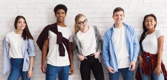 Stilfulla studenter som poserar över den vita väggen, skörd arkivbilder