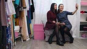 Stilfulla unga kvinnliga shoppare som tar en selfie på en mobiltelefon i ett märkes- boutiquesammanträdeslut som grinar tillsamma stock video