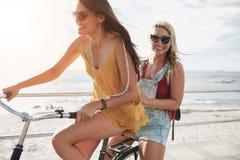 Stilfulla unga vänner som tillsammans rider på en cykel royaltyfri bild