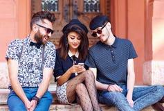 Stilfulla vänner som har gyckel samman med telefonen Arkivfoto