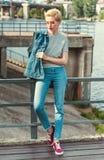 stilfullt attraktivt flickaanseende på bron i jeans arkivfoton
