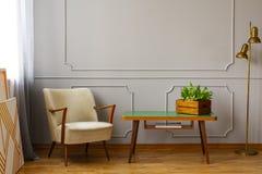 Stilfullt beige fåtöljanseende bredvid den lilla kaffetabellen med blommor på den och lampan bredvid den arkivfoton