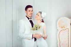 Stilfullt brud- och brudgumanseende i omfamning royaltyfri fotografi