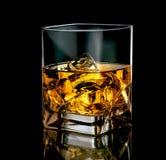 Stilfullt exponeringsglas av whisky med is på svart bakgrund arkivfoton