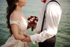 Stilfullt gift par som omfamnar i bakgrunden av havet royaltyfri foto