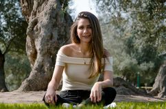 Stilfullt gladlynt brunettsammanträde under ett träd i en parkera fotografering för bildbyråer