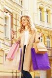 Stilfullt härligt blont hår som ler flickan med shopping genom att använda hennes telefon lycklig shopping Arkivfoton