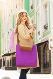 Stilfullt härligt blont hår som ler flickan med shopping genom att använda hennes telefon lycklig shopping Arkivbilder